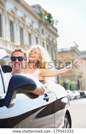 Cars - people driving car with male driver and happy woman passenger. Man driver wearing sunglasses. Young couple having fun in car driving on travel vacation road trip together.