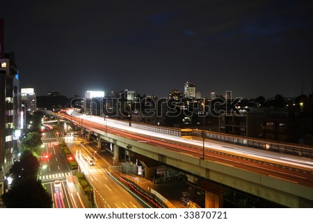 Cars racing at night on a highway and street in Tokyo, Japan - stock photo