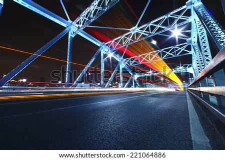cars run fast across the highway of colorful steel bridge at night - stock photo