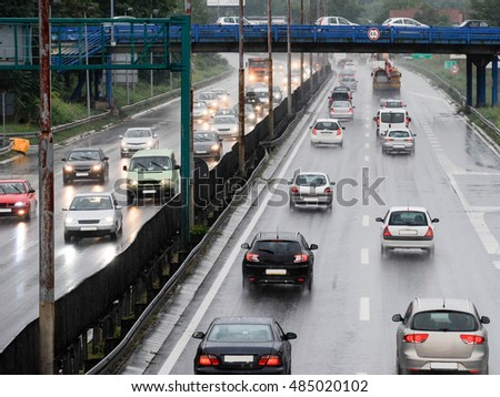 Cars rush on highway during rainy day