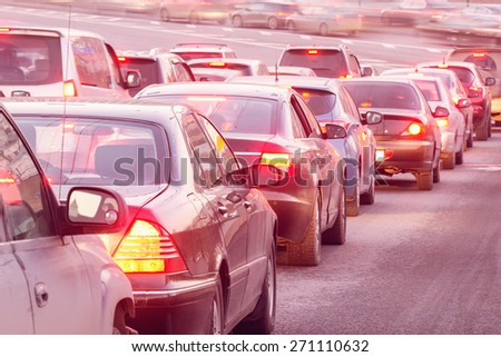 Cars stand before the trafficlight on the central city streets at sunset time. - stock photo