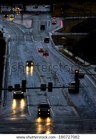 Cars with headlights shinning on stormy wet road driving in rain - stock photo