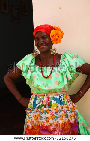 """CARTAGENA, COLOMBIA - JANUARY 14: """"Palenquera"""" woman sells fruit on January 14, 2010 in Cartagena, Colombia. Palenqueras are an african descendant ethnic group found in the north of South America. - stock photo"""
