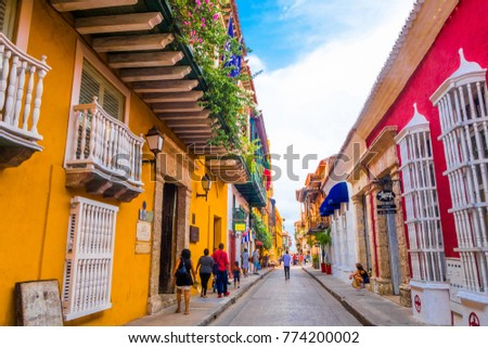 CARTAGENA, COLOMBIA 22, 2017: Unidentified people walking in Cartagena city street with colorful buildings of Cartagena Walled City