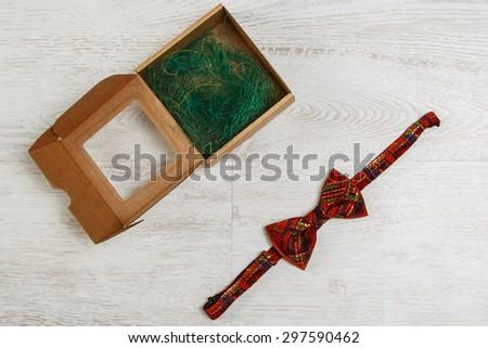 Carton box and bow tie on the floor - stock photo