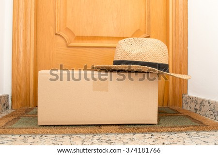 carton box on the floor of entry home with a summer hat over the package as vacations concept - stock photo