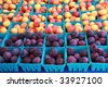 Cartons of fresh plums and nectarines for sale at the local farmer's market - stock photo