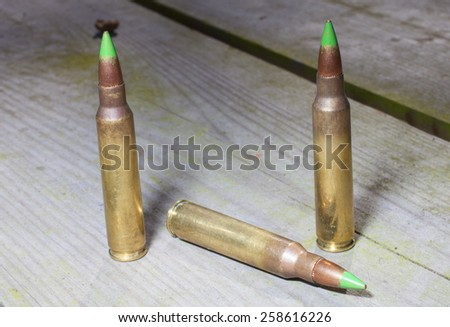 Cartridges that are loaded with bullets with a green tip - stock photo