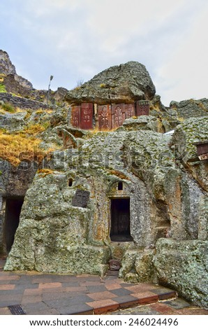 carved cross on ancient stone wall of medieval geghard monastery in Armenia - stock photo