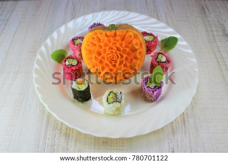 Carved Flower In Pumpkin As Plate Decoration And Purple Sushi Roll Pink White