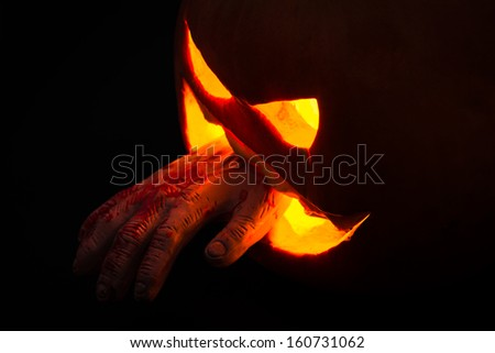 Carved halloween pumpkin with a bloody hand. The spooky and creepy fall tradition of Halloween - stock photo