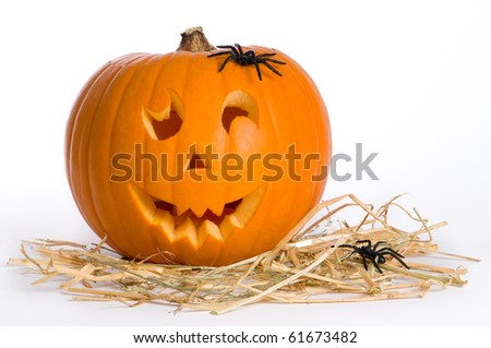 Carved Jack O Lantern on straw with spiders - stock photo