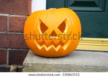 Carved pumpkin on a doorstep, isolated. - stock photo