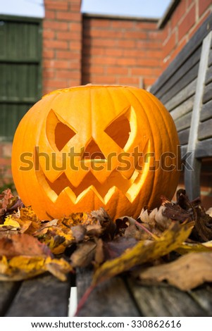 Carved pumpkin on a gardgen bench surrounded by leaves.  Isolated. - stock photo