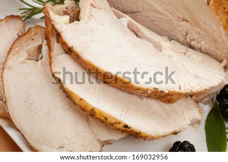 Carved Rosemary-basil rub roasted turkey breast garnished with grapes, blackberies, and fresh basil, and rosemary in fall themed surrounding.  - stock photo