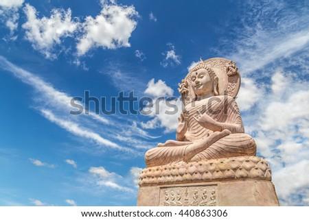Carved sandstone Buddha statue on blue sky background - stock photo