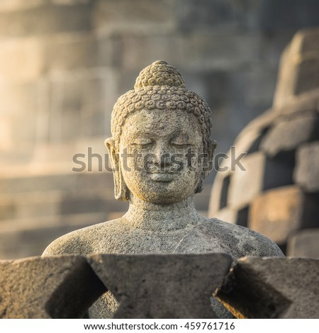 Carved stone buddha statue in small stupa around top of Borobudor, world largest buddhist temple in Yogyakarta, Indonesia.
