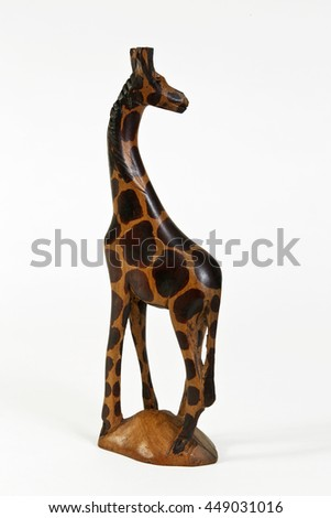 Carved wooden standing giraffe looking over to the right