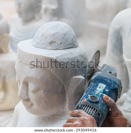 carvers using a tool on a marble to carve a statue Buddha in Mandalay of Myanmar. - stock photo