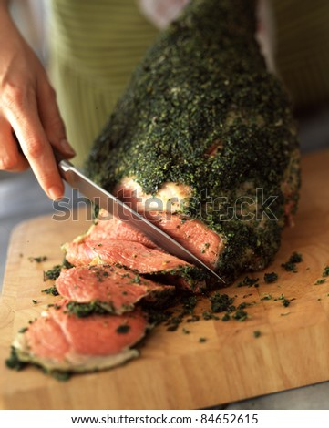 Carving a leg of lamb with herbs - stock photo
