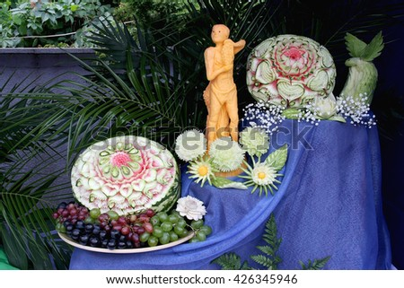 Carving on fresh vegetables and fruit: composition, consisting of watermelon, pumpkin, cucumbers and other vegetables and fruit - stock photo