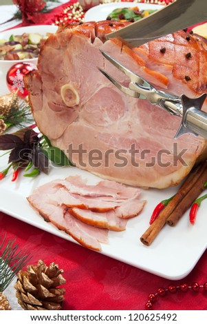 Carving roasted spiced ham on holiday dinning table, garnished with cloves, cinnamon sticks, hot chili pepper, and purple basil. Side dishes and Christmas ornaments around. - stock photo