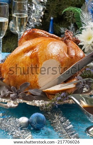 Carving roasted turkey garnished with herbs on blue Christmas decorations, and champagne. Christmas tree as background.  - stock photo