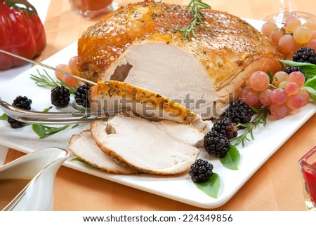 Carving Rosemary-basil rub roasted turkey breast garnished with grapes, blackberies, and fresh basil, and rosemary in fall themed surrounding.  - stock photo