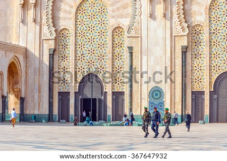 CASABLANCA, MOROCCO, APRIL 2, 2015: Local security officers walk on the outside grounds of Hassan II Mosque or Grande Mosquee Hassan II