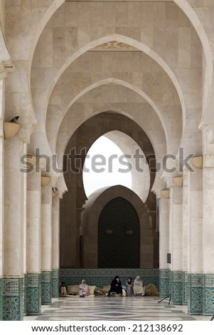 CASABLANCA, MOROCCO - JULY 23: Local people sitting at a door of King Hassan II Mosque on July 23, 2014 in Casablanca, Morocco. It is the largest Mosque in the country - stock photo