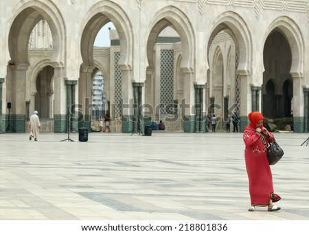 CASABLANCA, MOROCCO - JULY 23: Local woman walking at the King Hassan II Mosque on July 23, 2014 in Casablanca, Morocco. It is the largest Mosque in the country  - stock photo