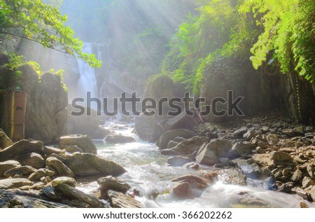 Cascade and waterfall in a mysterious forest with sunlight shining through the lavish greenery ~ Beautiful river scenery of Taiwan - stock photo