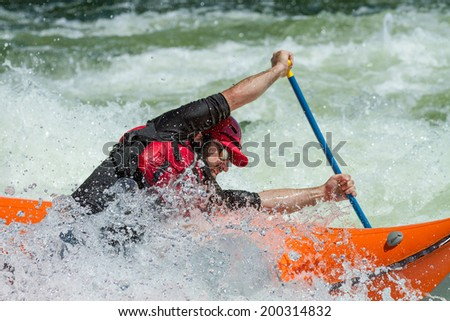 CASCADE, IDAHO/USA - JUNE 21, 2014: Boater stuck in the wave and trying to paddle out during the Payette River Games