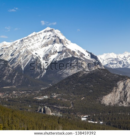 Cascade Mountain dwarfs the town of Banff and the Banff Fairmont Springs Hotel at Banff National Park, Canada - stock photo