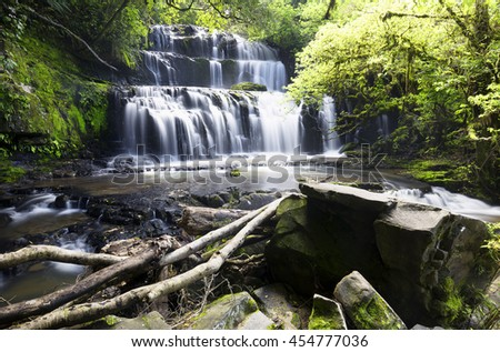 Cascaded waterfall surrounded by green forest. - stock photo