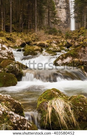 Cascading mountain creek in deep forest with tall waterfall on background, early spring, waterfall Leuenfall, Switzerland - stock photo