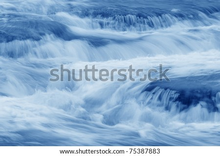 Cascading stream in shades of blue. - stock photo