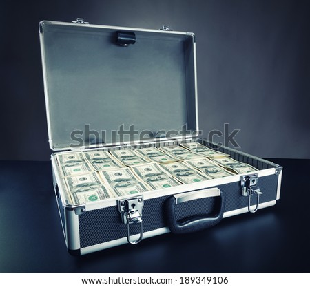 Case full of money on gray background - stock photo