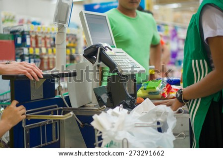 Cash desk with cashier serving customers in supermarket