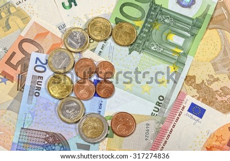 Cash euro coins and banknotes, shallow DOF - stock photo