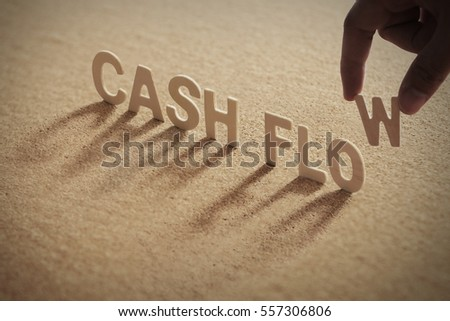 CASH FLOW wood word on compressed or cork board with human's finger at W letter.