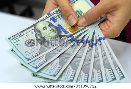 Cash in hands. Profits, savings. Stack of dollars. Woman counting money. Dollars in Woman's hands. Woman in business clothes with dollars. Success, motivation, financial flows, wealth. - stock photo