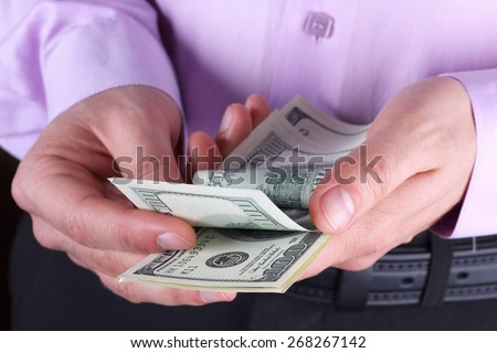 Cash in hands. Stack of dollars. Man counting money. Dollars in man's hands. A man in business clothes with dollars. Success, motivation, financial flows, wealth. Stack of dollars. Profits, savings. - stock photo