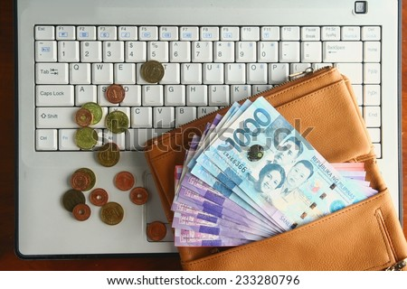 Cash money in a leather wallet and coins on a laptop computer Photo of a bunch of cash money in a leather wallet and coins on a laptop computer - stock photo