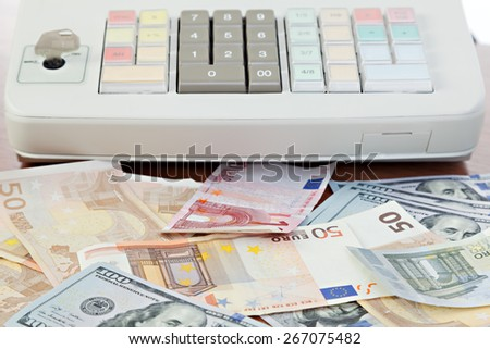Cash register and different paper currencies foreground - stock photo