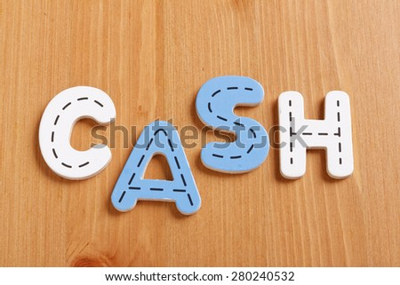 CASH, spell by woody puzzle letters with woody background - stock photo