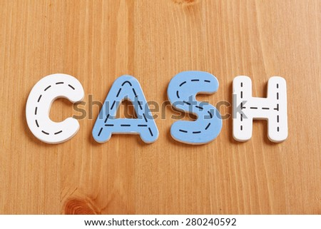 CASH, spell by woody puzzle letters with woody background