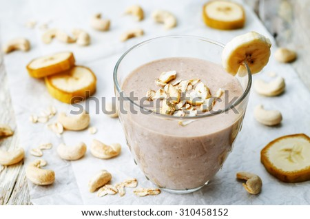 cashew banana cocoa oats smoothie on a white wood background. the toning. selective focus - stock photo