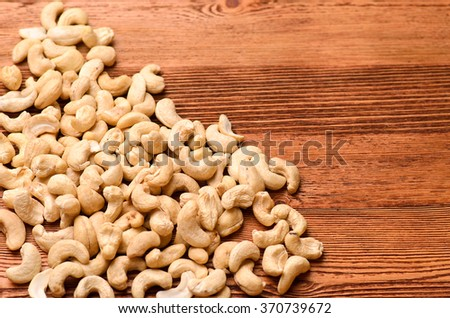 Cashew nuts scattered on a brown wooden table, close-up - stock photo