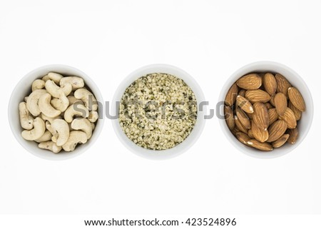 Cashews, hemp meal and unblanched almonds in bowls, on white background - stock photo